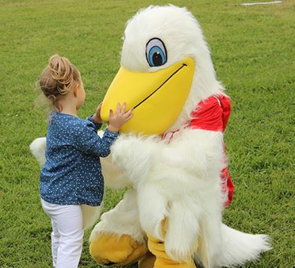 A pelican mascot kneeling next to a young child