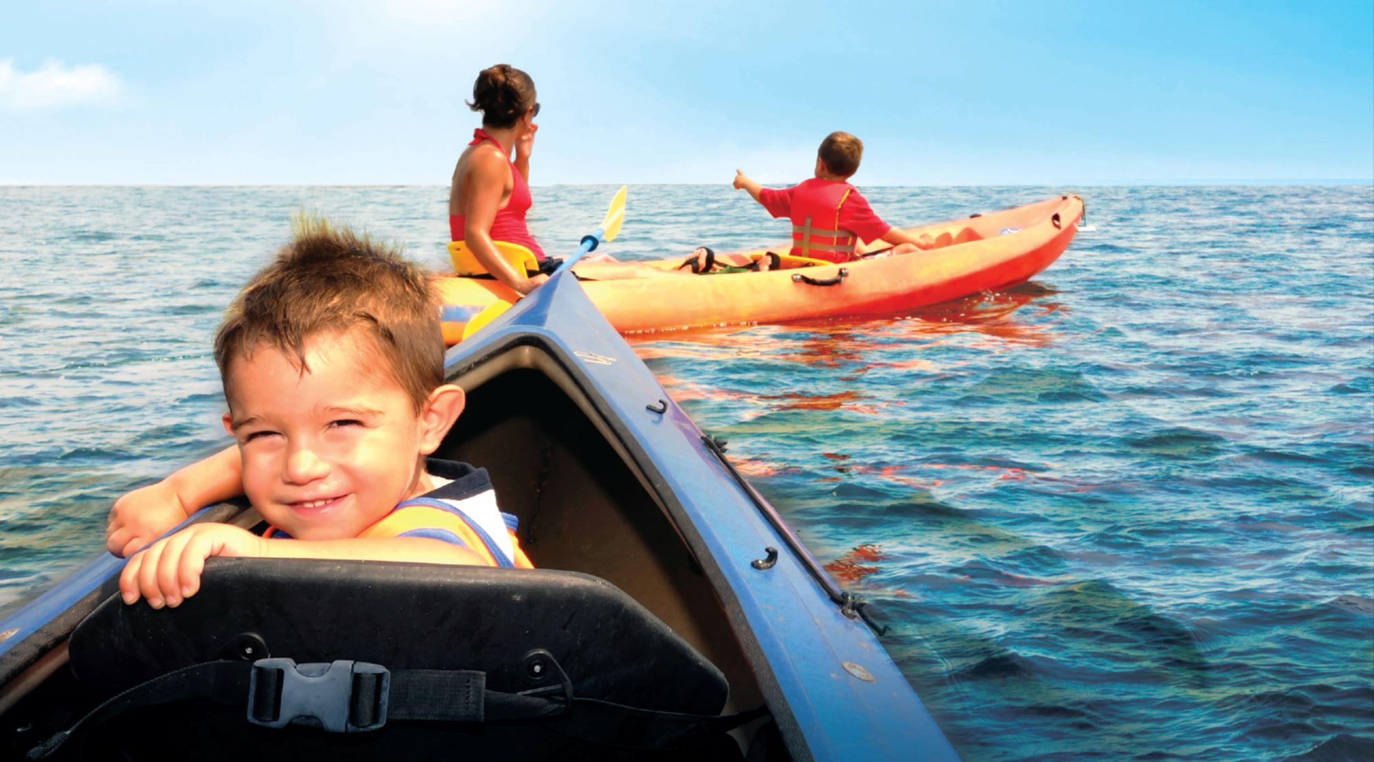 Boy riding in kayak with his family on a lake