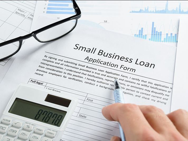 Photo of someone filling out small business loan form